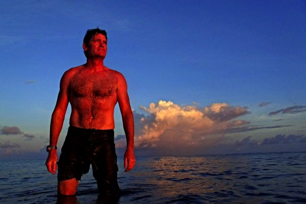 Craig Leeson stands in ocean with sunset