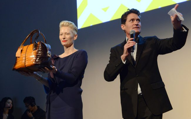 Speaker Craig Leeson on stage with Tilda Swinton