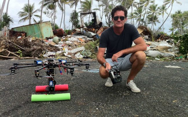 Craig Leeson kneels next to drone with wreckage behind