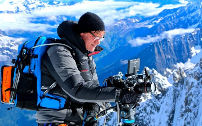 Filmmaker Craig Leeson filming on a mountain in Switzerland.